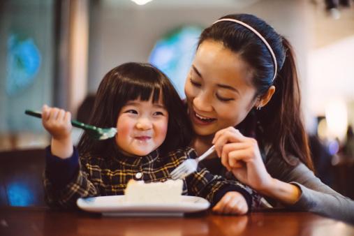 Mom & toddler girl having cake joyfully in cafe - gettyimageskorea