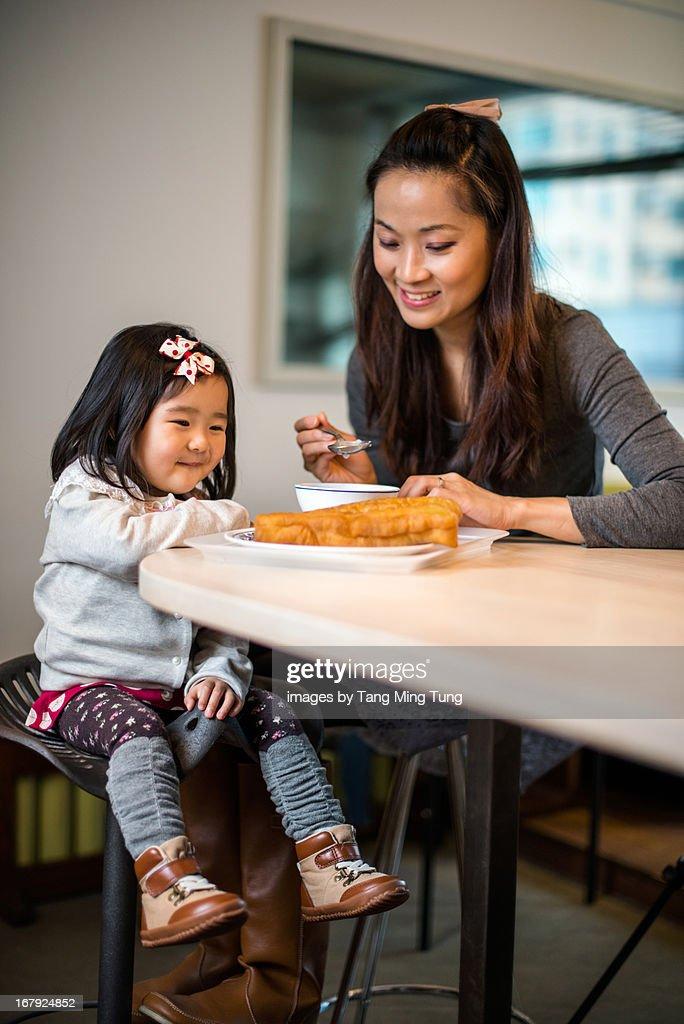 Mom & toddler girl having chinese breakfast : Stock Photo