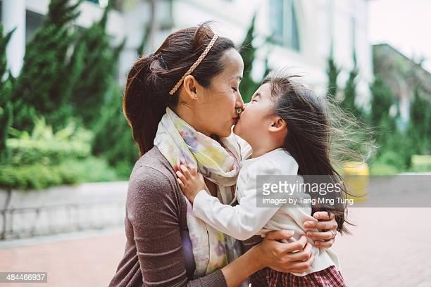 Mom & toddler girl hugging & kissing joyfully