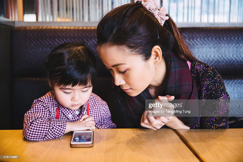 Mom & toddler girl looking at smartphone : Stock Photo