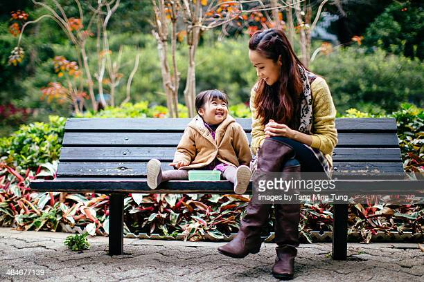 Mom & toddler girl talking joyfully in the park
