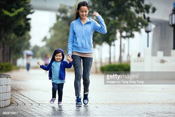Mom & toddler girl walking through the drizzle