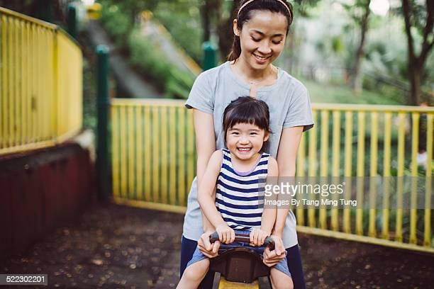 Mom & toddler playing seesaw joyfully in park