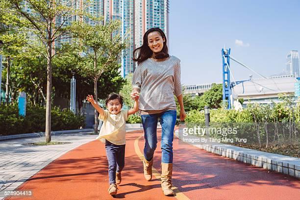 Mom & toddler running joyfully on track
