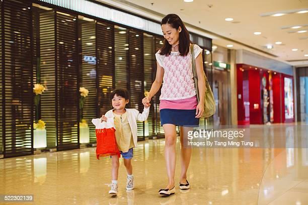 Mom & toddler shopping joyfully in shopping mall