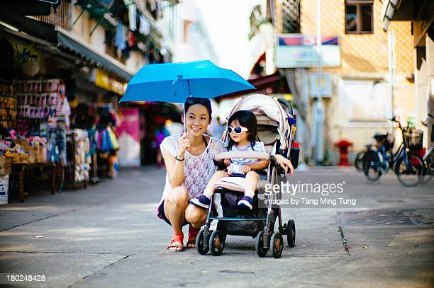 Mom & toddler strolling on street with stroller