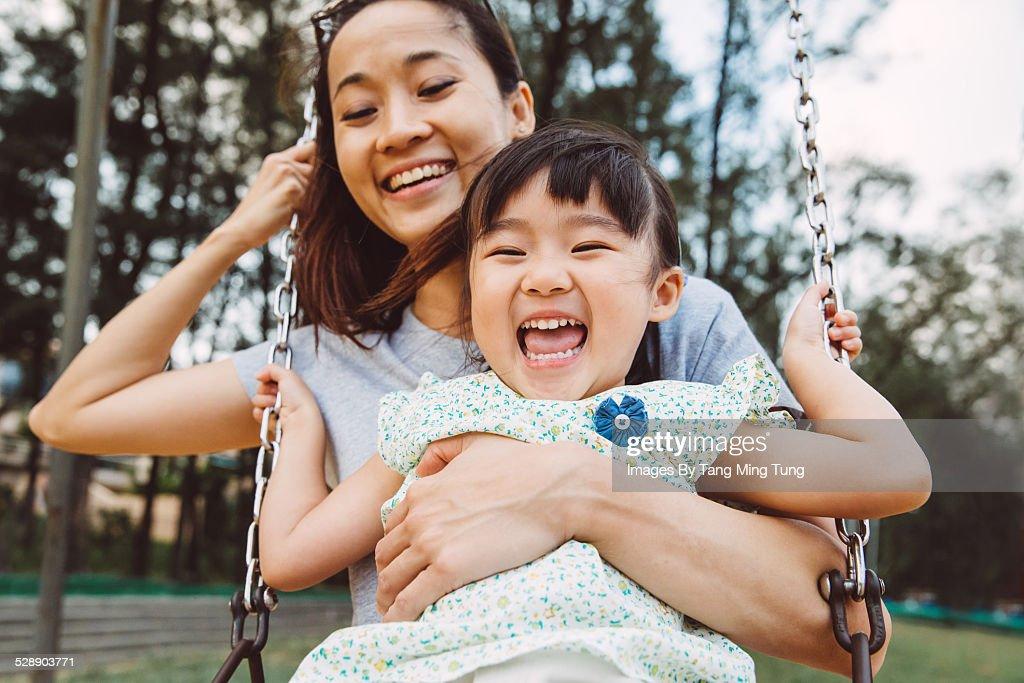 Mom & toddler swinging on swing joyfully in park : Stock Photo