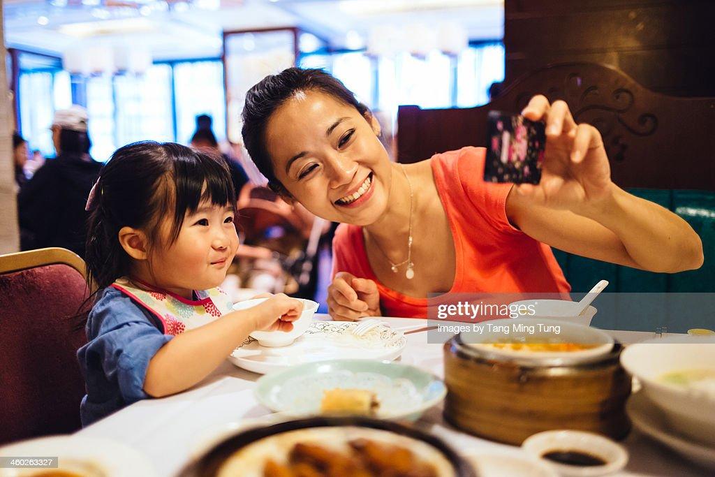 Mom & toddler taking selfie in Chinese restaurant : Stock Photo