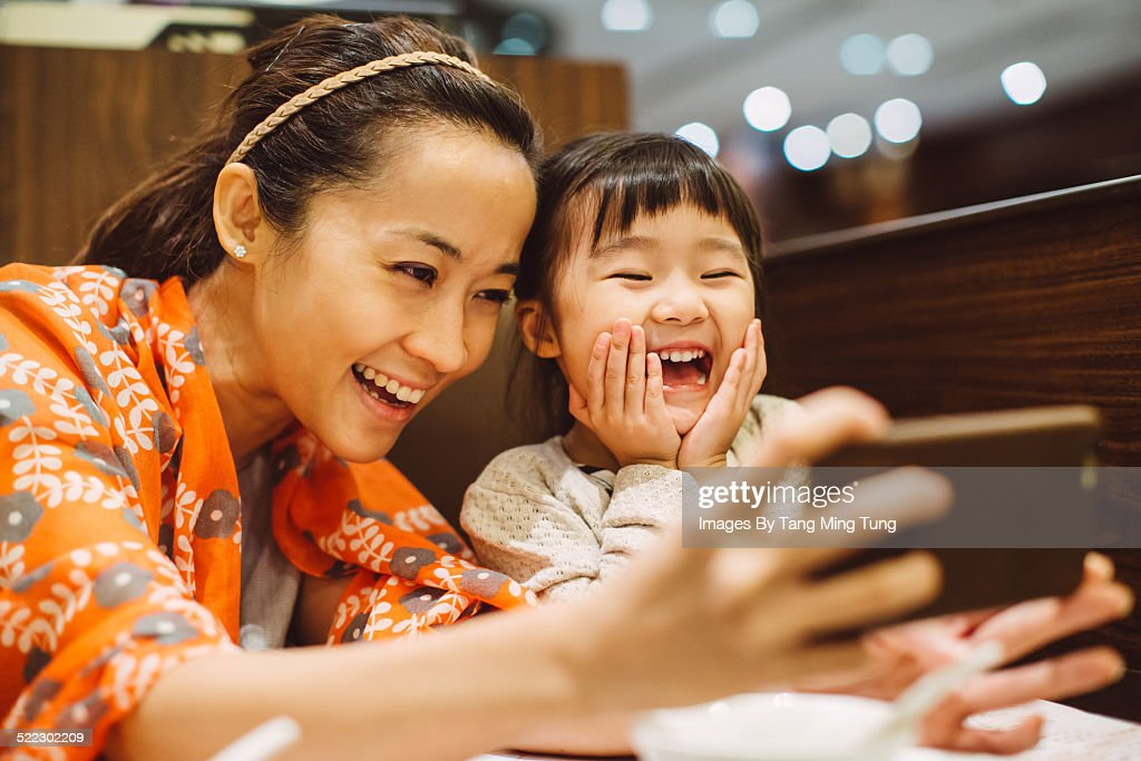 Mom & toddler taking selfies in restaurant : Stock Photo