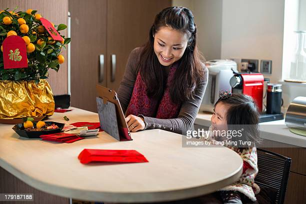 Mom & toddler using tablet in Chinese New Year