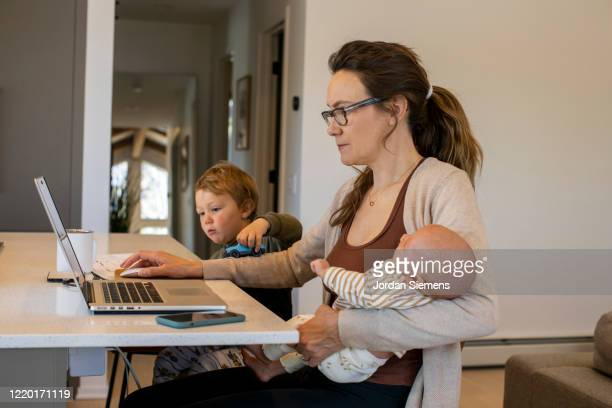 a mom trying to work from home while holding her daughter and watching her son during the covid-19 home quarantine. - authenticity stock pictures, royalty-free photos & images