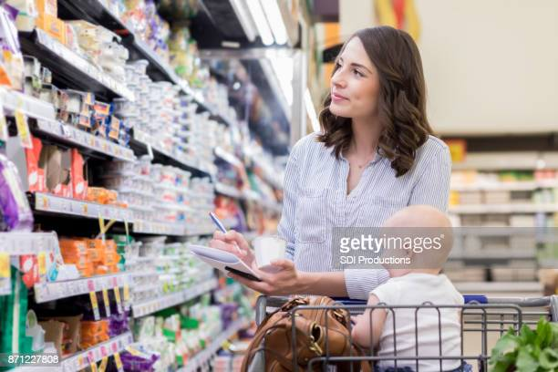 Mom uses grocery list while shopping in supermarket