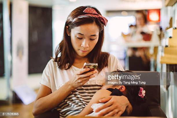 Mom using smartphone while holding child to sleep