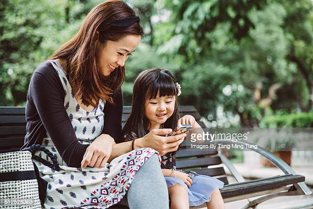 Mom using smartphone with child in park