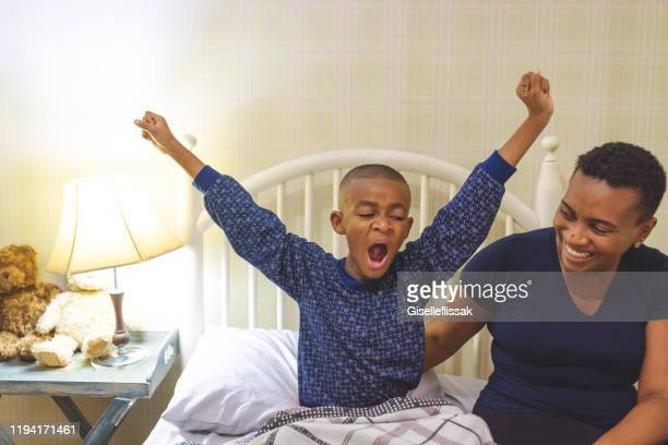 mom waking the son up in the bedroom in the morning - yawning mother child stock photos and pictures