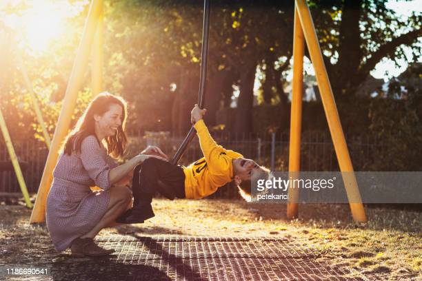 mom will always be around to support her little prince - britain playgrounds stock pictures, royalty-free photos & images