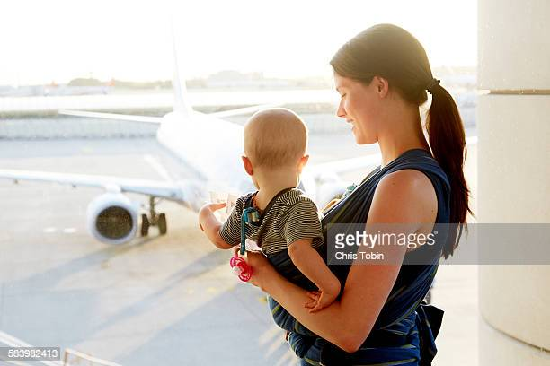 Mom with baby looking at plane at an airport