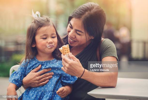 mom with child eating ice cream cone - filipino family stock pictures, royalty-free photos & images