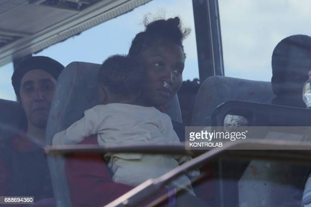 A mom with her baby on autobus after landing from the Ship Acquarius of ItalianFrancoGerman humanitarian organization «Sos Mediterranee» in...