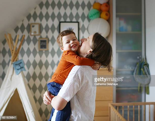 a mom with her son in her arms - nursery bedroom stock pictures, royalty-free photos & images