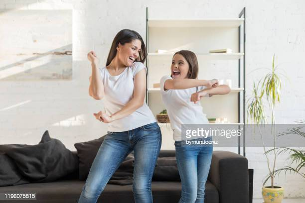 mom with kid girl dancing in living room - dancing stock pictures, royalty-free photos & images