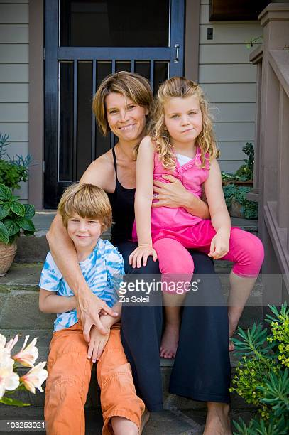 mom with two small children on porch - mom sits on sons lap stock pictures, royalty-free photos & images