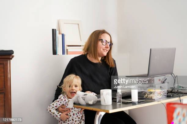mom working from home fending off her child while on a conference call - working stock pictures, royalty-free photos & images
