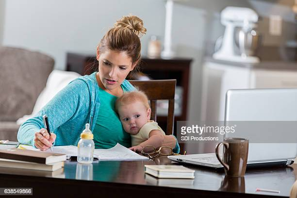 Mom works on college assignment while cuddling with infant daughter