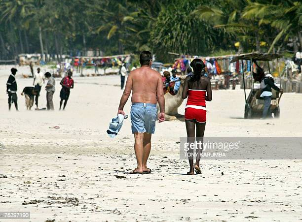 TO GO WITH AFP STORY KENYATOURISMEPROSTITUTIONENFANTS by Beatrice Debut Photo taken 19 June 2007 shows a mixedrace couple walking on a beach at...