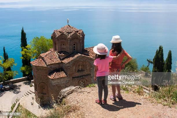 moment of encouragement, for two sisters, for sight sveti (saint) jovan kaneo church on lake ohrid, macedonia - macedonië land stockfoto's en -beelden