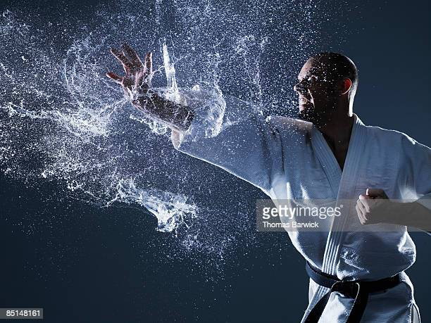 moment of impact of martial artists hand and water - martial arts stock photos and pictures