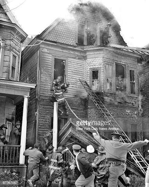 Moment of Suspense Firemen Anthony Tavolacci grabs a window ledge as porch roof collapses under him in blaze at 78 E 236th St Bronx Buddies pulled...