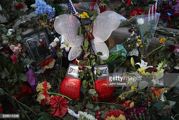 Momentos including a pair of boxing gloves lie at a makeshift memorial for Muhammad Ali outside the Muhammad Ali Center on June 8 2016 in Louisville...