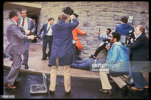 Moments after attempted murder of Pres. Reagan by John Hinckley w. WH press secy. James Brady on ground shot, secret service w. Guns drawn, & camera...