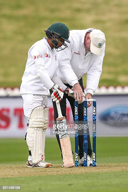 Mominul Haque of Bangladesh helps Umpire Paul Reiffel of Australia reset the bails after they were blown off by a gust of wind during day one of the...