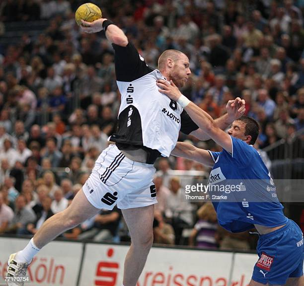 Momir Ilic of Gummersbach tackles Ales Pajovic of Kiel during the Handball Bundesliga game between VfL Gummersbach and THW Kiel at the Koelnarena on...