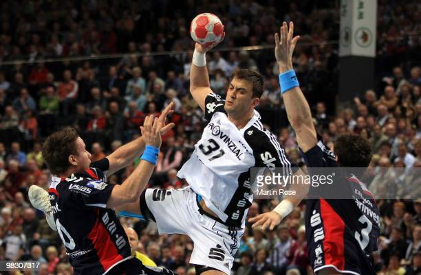 Momir Ilic of Kiel challenges Tobias Karlsson and Thomas Mogensen of FlensburgHandewitt for the ball during the Toyota Handball Bundesliga match...