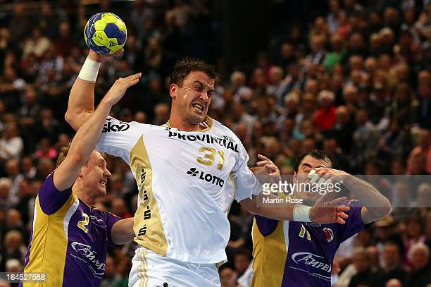 Momir Ilic of Kiel challenges Vasily Filippov and Sergiy Shelmenko of Medvedi for the ball during the EHF Champions League second leg round of...