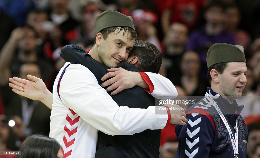 Momir Ilic of Serbia embraces an official on the podium after losing 19-21 the Men's European Handball Championship final match between Serbia and Denmark at Beogradska Arena on January 29, 2012 in Belgrade, Serbia.