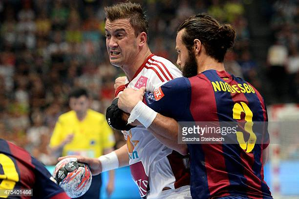 Momir Ilic of Veszprem is challenged by Jesper Brain Noeddesbo of Barcelona during the 'VELUX EHF FINAL4' final match between FC Barcelona and MKBMVM...