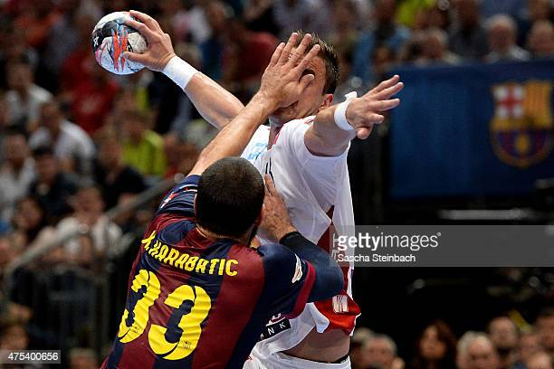 Momir Ilic of Veszprem is challenged by Nikola Karabatic of Barcelona during the 'VELUX EHF FINAL4' final match between FC Barcelona and MKBMVM...