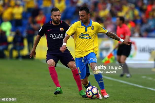 Momo of Las Palmas looks to hold off the incoming challenge from Jordi Alba of Barcelona during the La Liga match between UD Las Palmas and Barcelona...