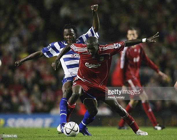 Momo Sissoko of Liverpool holds off a challenge from Andre Bikey of Reading during the Carling Cup third round match between Liverpool and Reading at...
