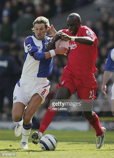 Momo Sissoko of Liverpool holds off a challenge from Robbie Savage of Blackburn Rovers during the Barclays Premiership match between Blackburn Rovers...