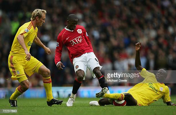 Momo Sissoko of Liverpool slides in to challenge Louis Saha of Manchester United for the ball during the Barclays Premiership match between...