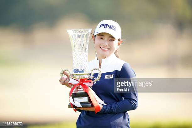 Momo Yoshikawa of Japan holds the winner's trophy after winning the rashink×RE SYU RYU/RKB Ladies at the Queens Hill Golf Club on March 27 2019 in...