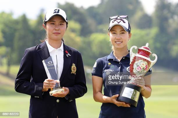 Momoko Ueda of Japan lifts the trophy with best amature winner Momoko Osato of Japan during a ceremony following the Chukyo Television Bridgestone...