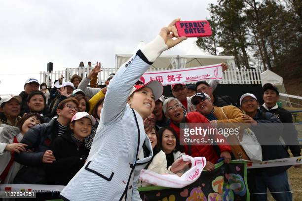 Momoko Ueda of Japan takes a selfie with fans during the ceremony following the TPoint x ENEOS Golf Tournament at Ibaraki Kokusai Golf Club on March...