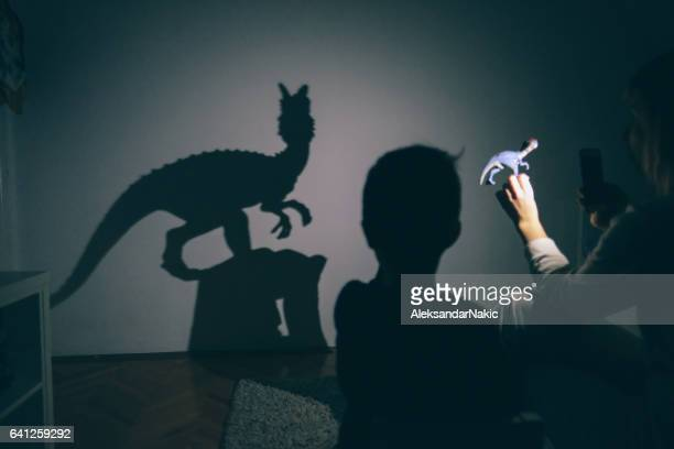 mom's shadow puppet show - dinosaur stock pictures, royalty-free photos & images