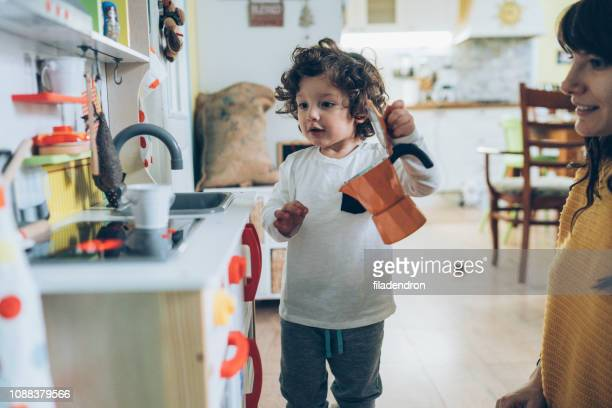 mon and boy playing in toy kitchen - gender stereotypes stock pictures, royalty-free photos & images
